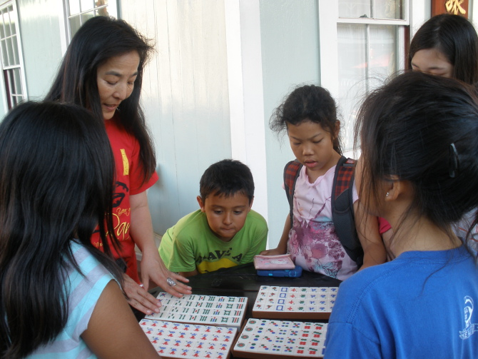 Kids learn to play Chinese game of Mahjong